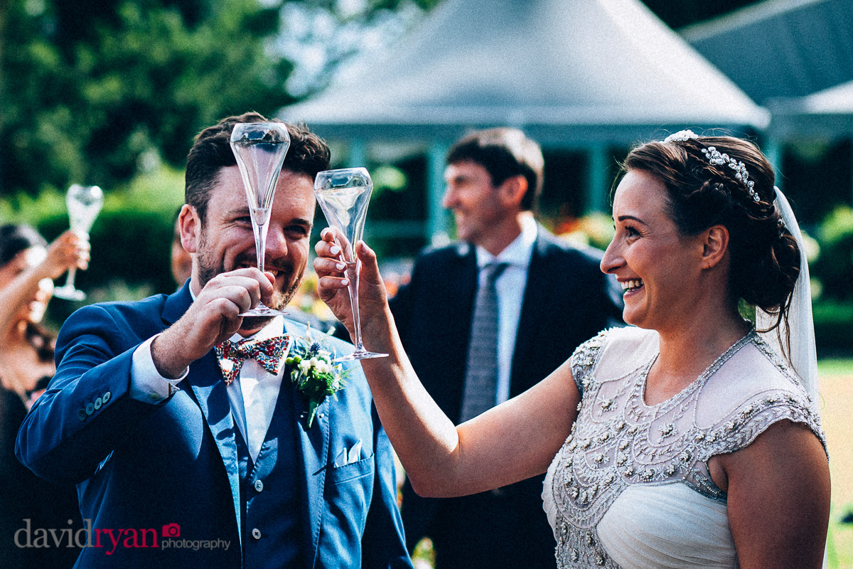 bride and groom toast on the lawn at virginia park lodge wedding