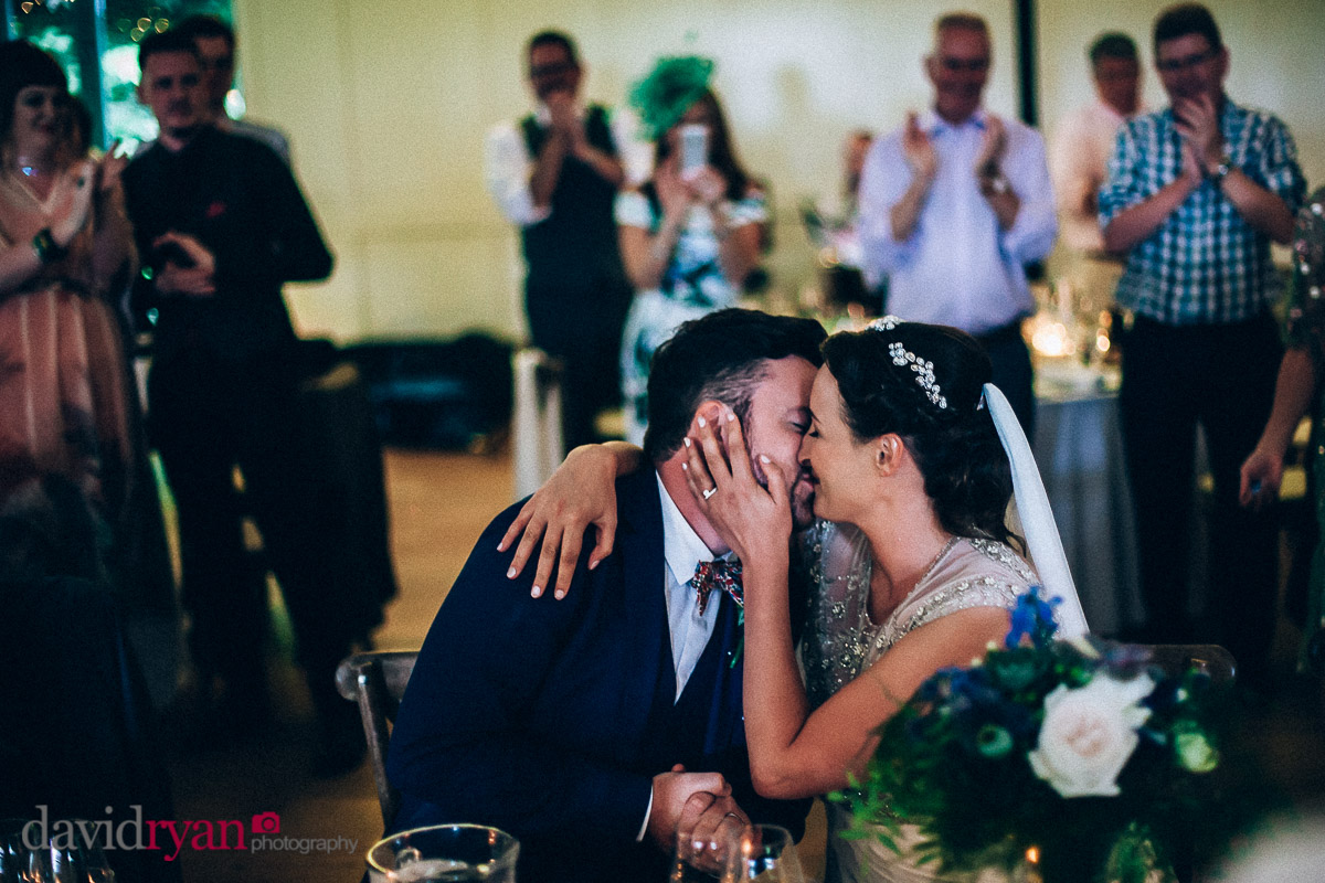 the bride and groom kiss during dinner at virginia park lodge