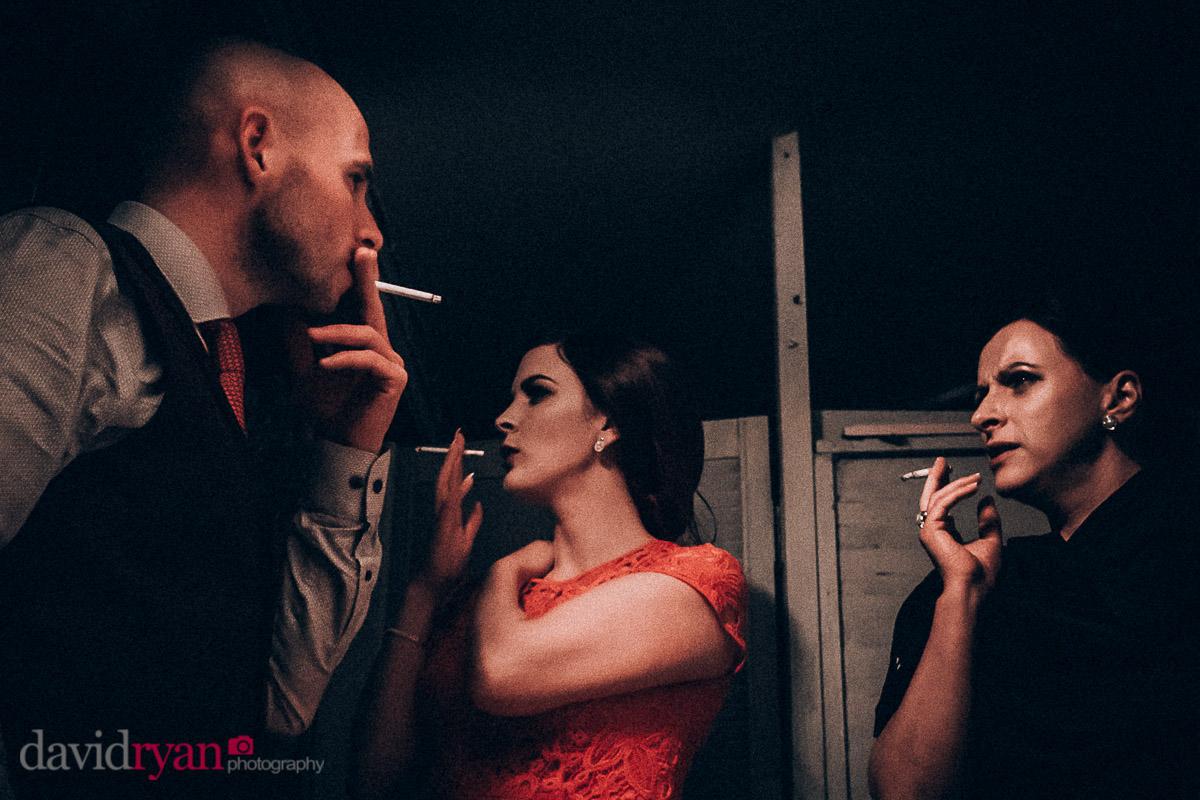 three people smoking at wedding