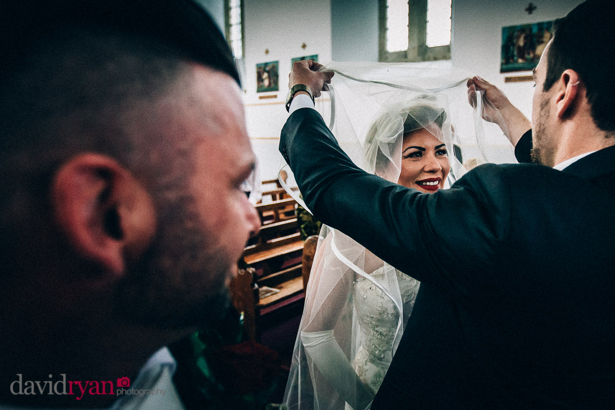 brides veil is lifted by her brother
