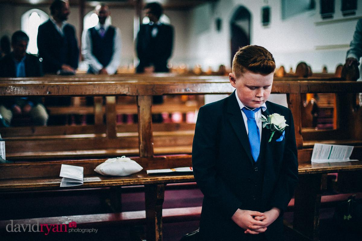 little boy prays at wedding in church