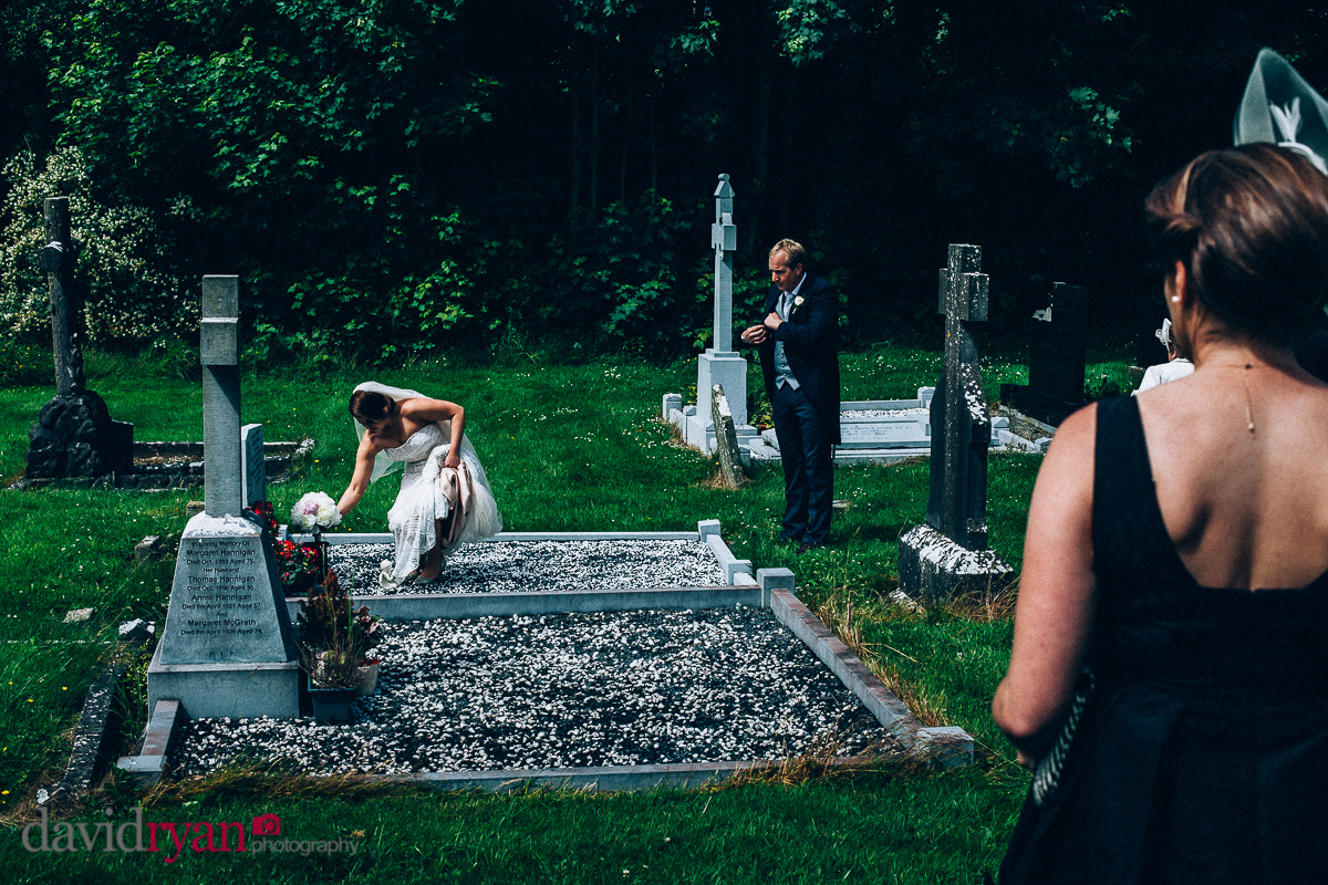 bride putting flowers on her mother's grave