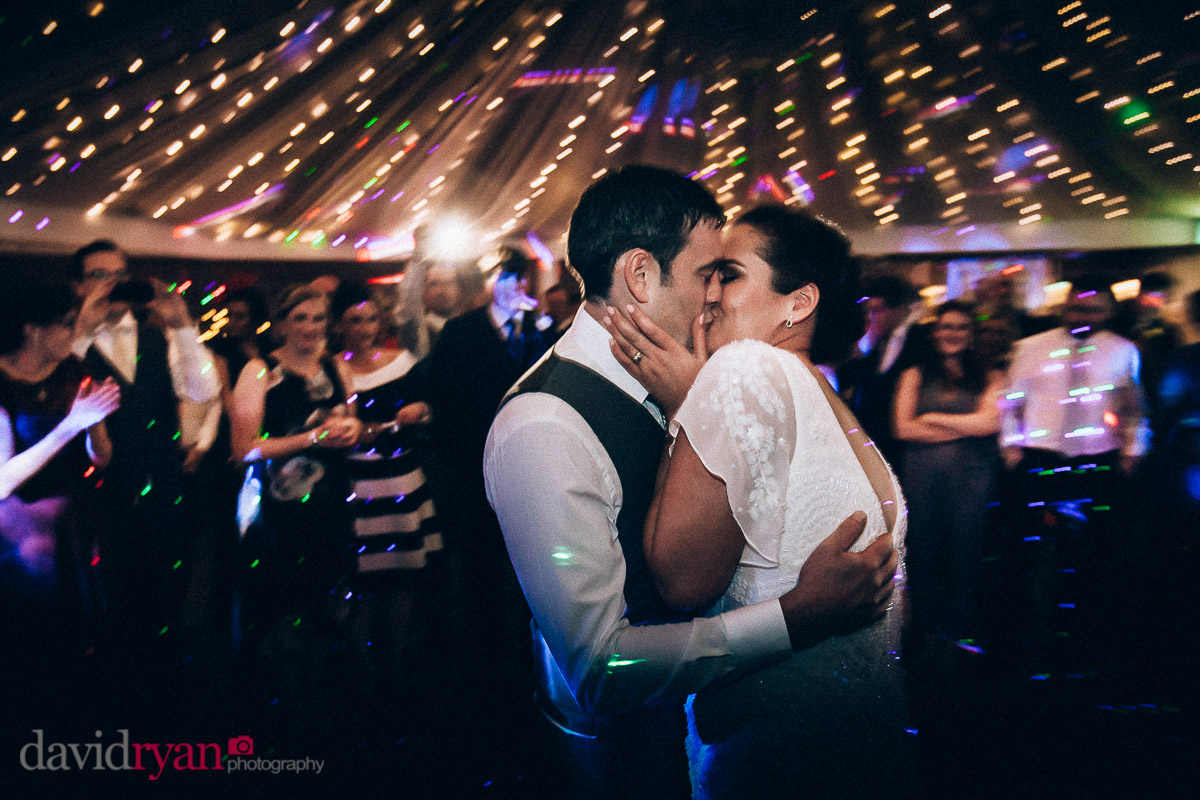 bride and groom kiss on dancefloor