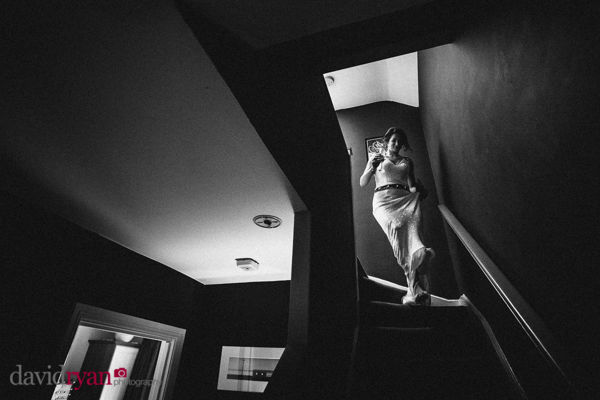 bride in wedding dress coming down stairs