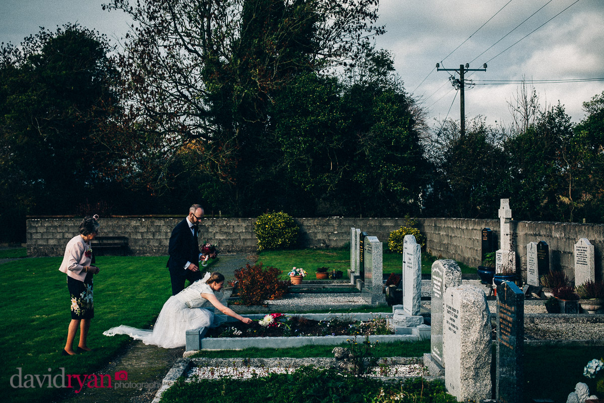 bride putting flowers on a grave