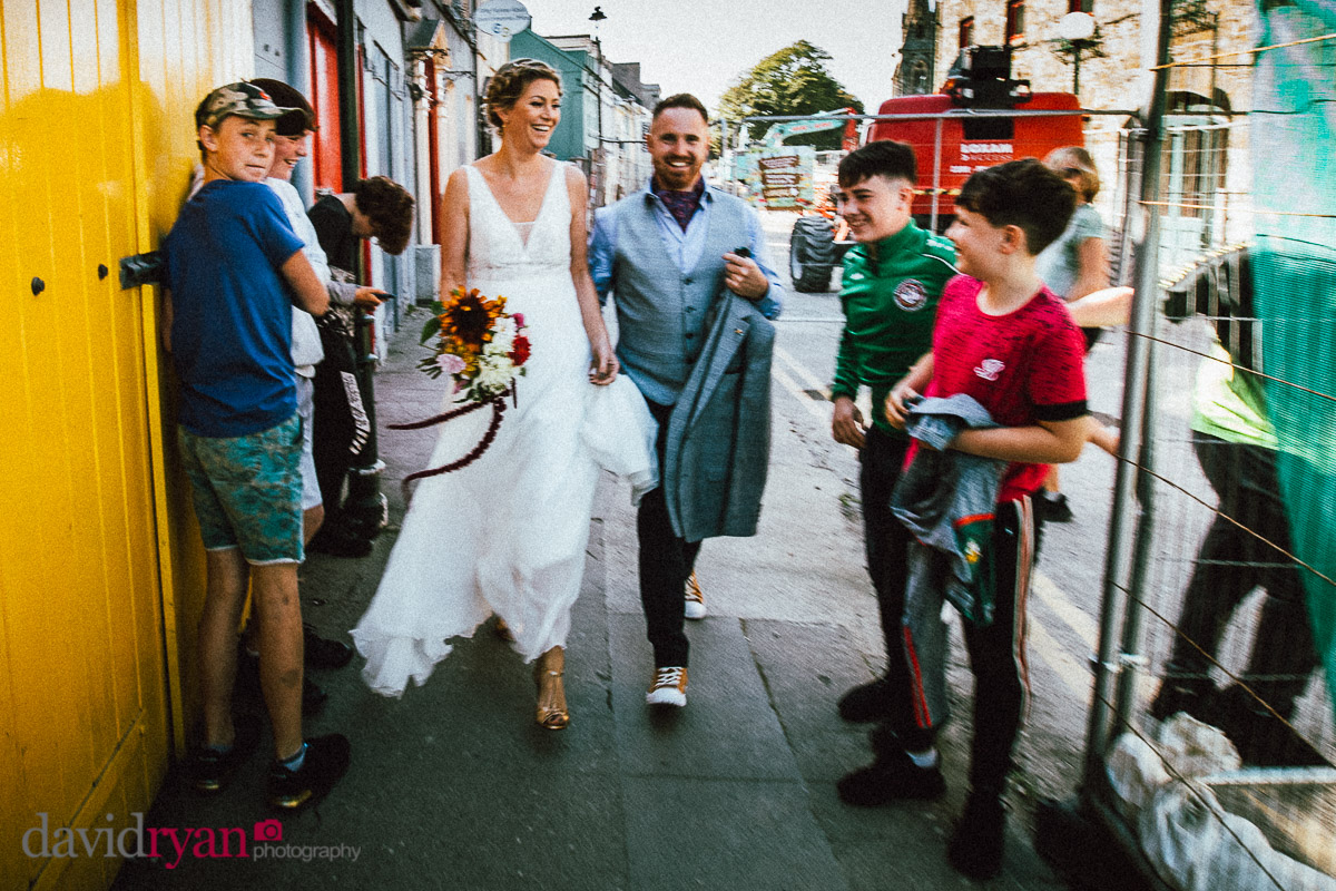 bride and groom walking down a street